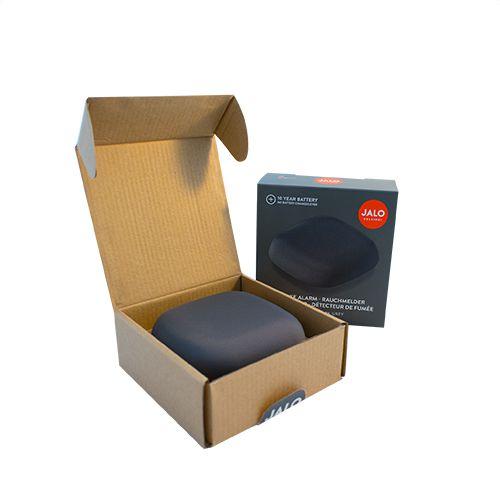 Pelēks dūmu detektors kastītes formā kastītē